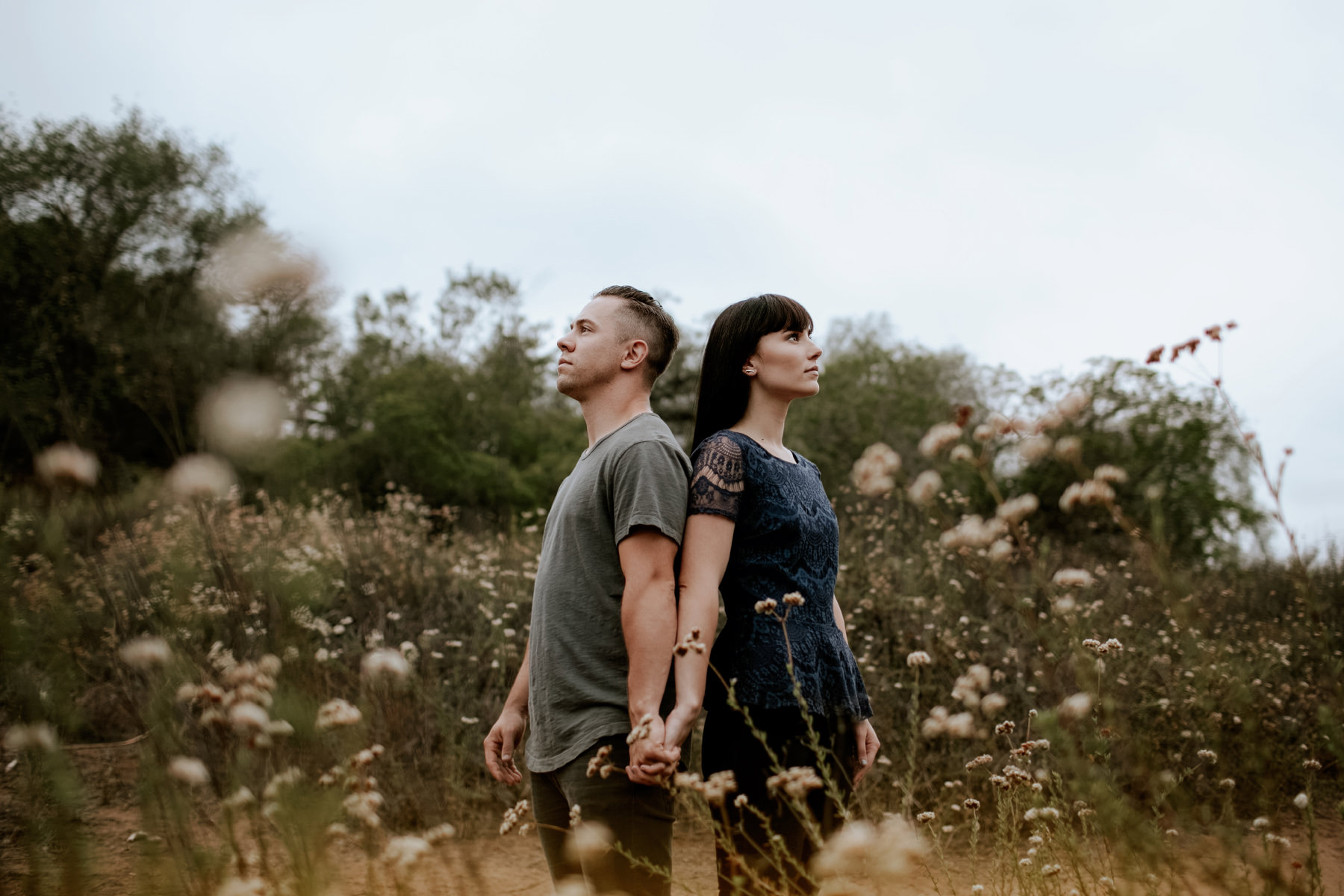 Engaged couple posing back to back in field of wildflowers at Felicita Park in Escondido