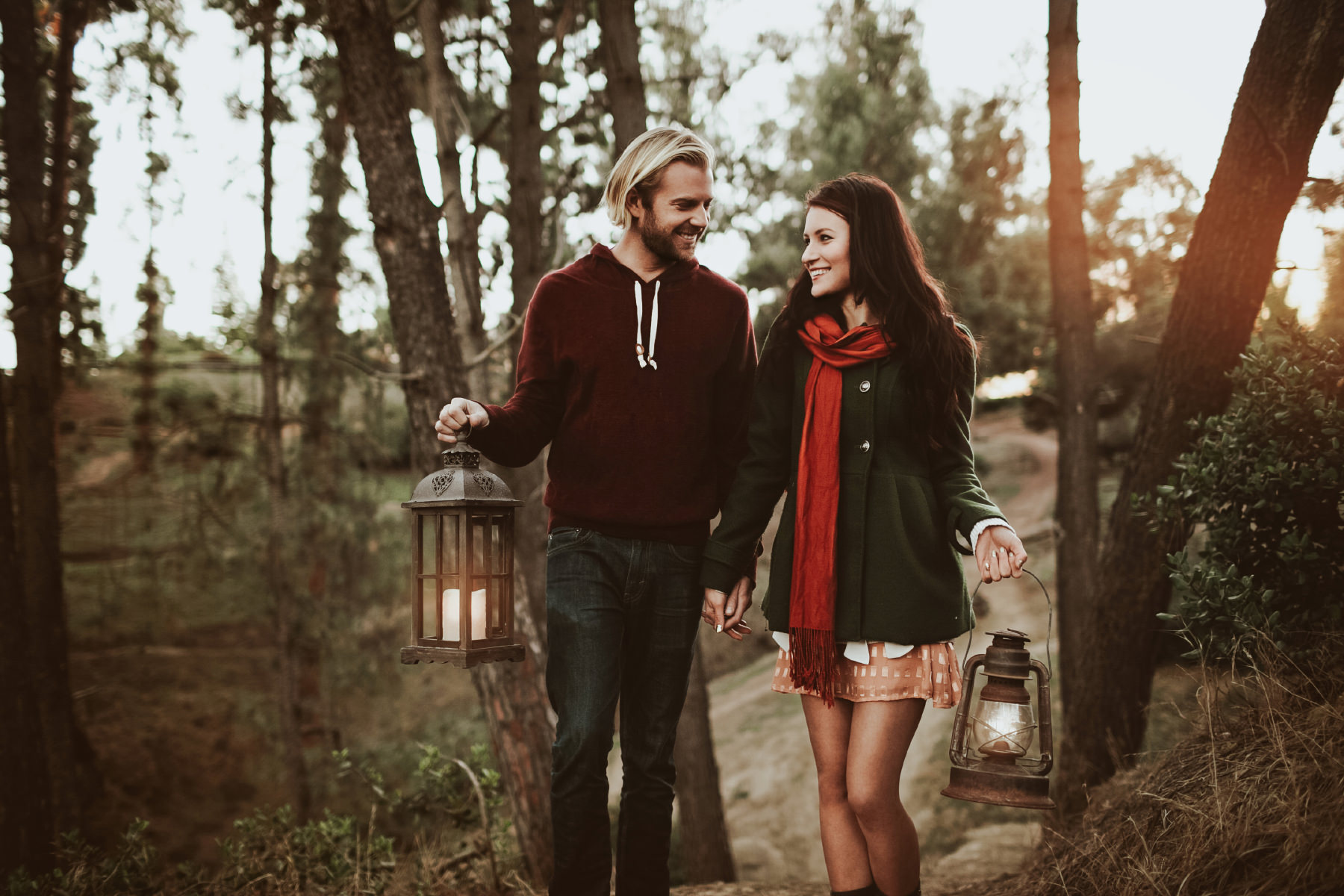 Engaged couple walking through the redwood trees of Bridle Trail with lanterns