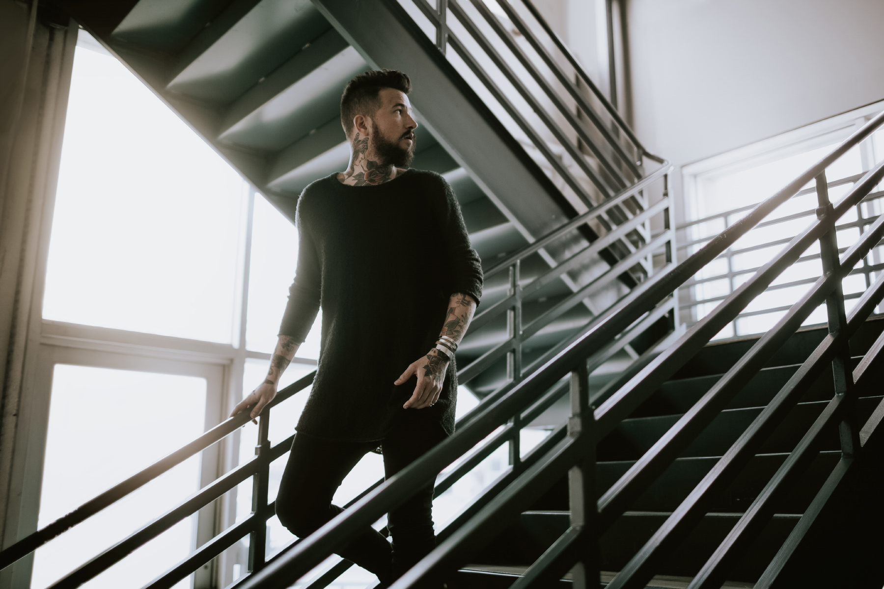 Tattooed bearded male model Tyler Ross wearing all black walking down parking garage stairs