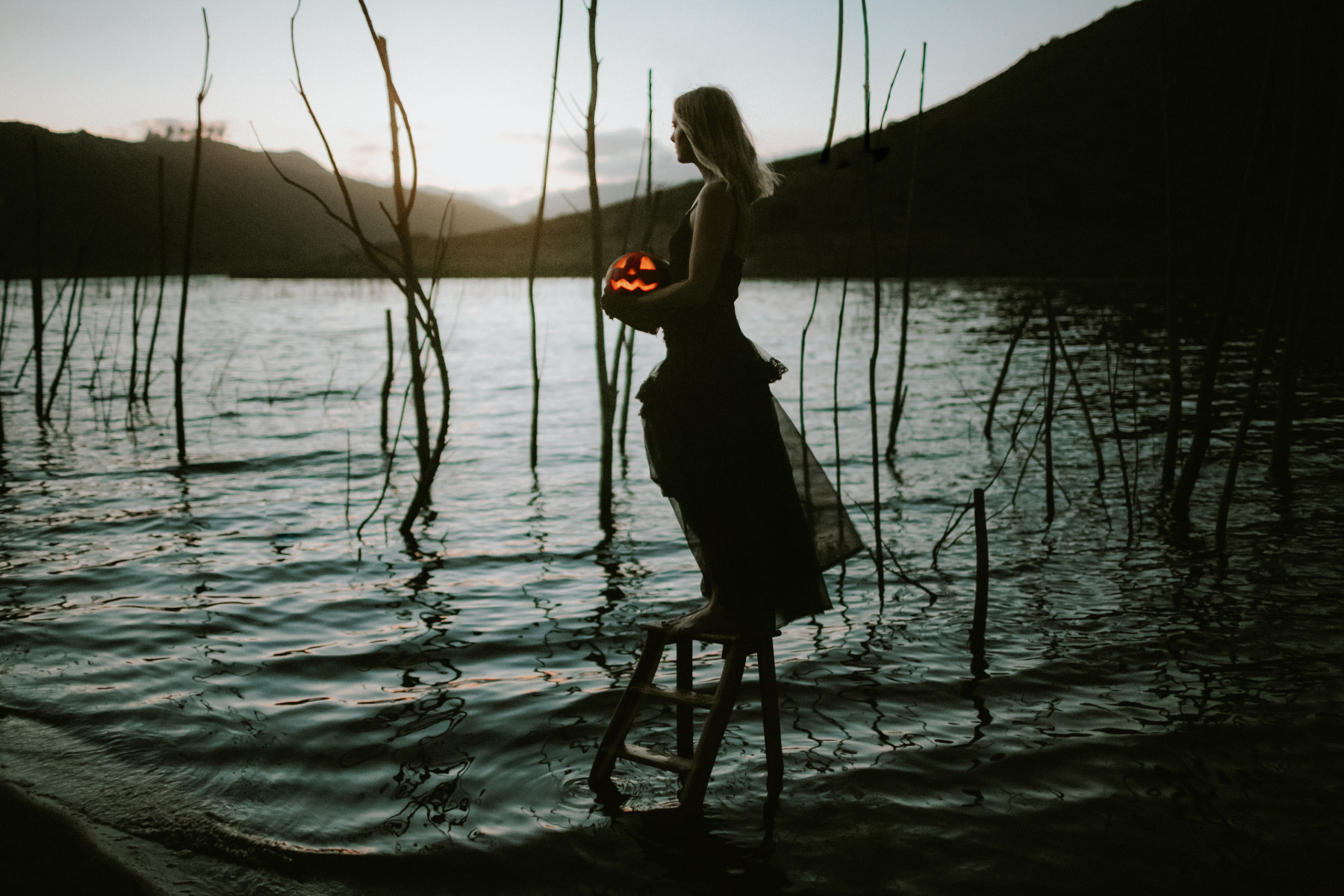 Model standing in a lake at sunset during Halloween holding a jack o lantern