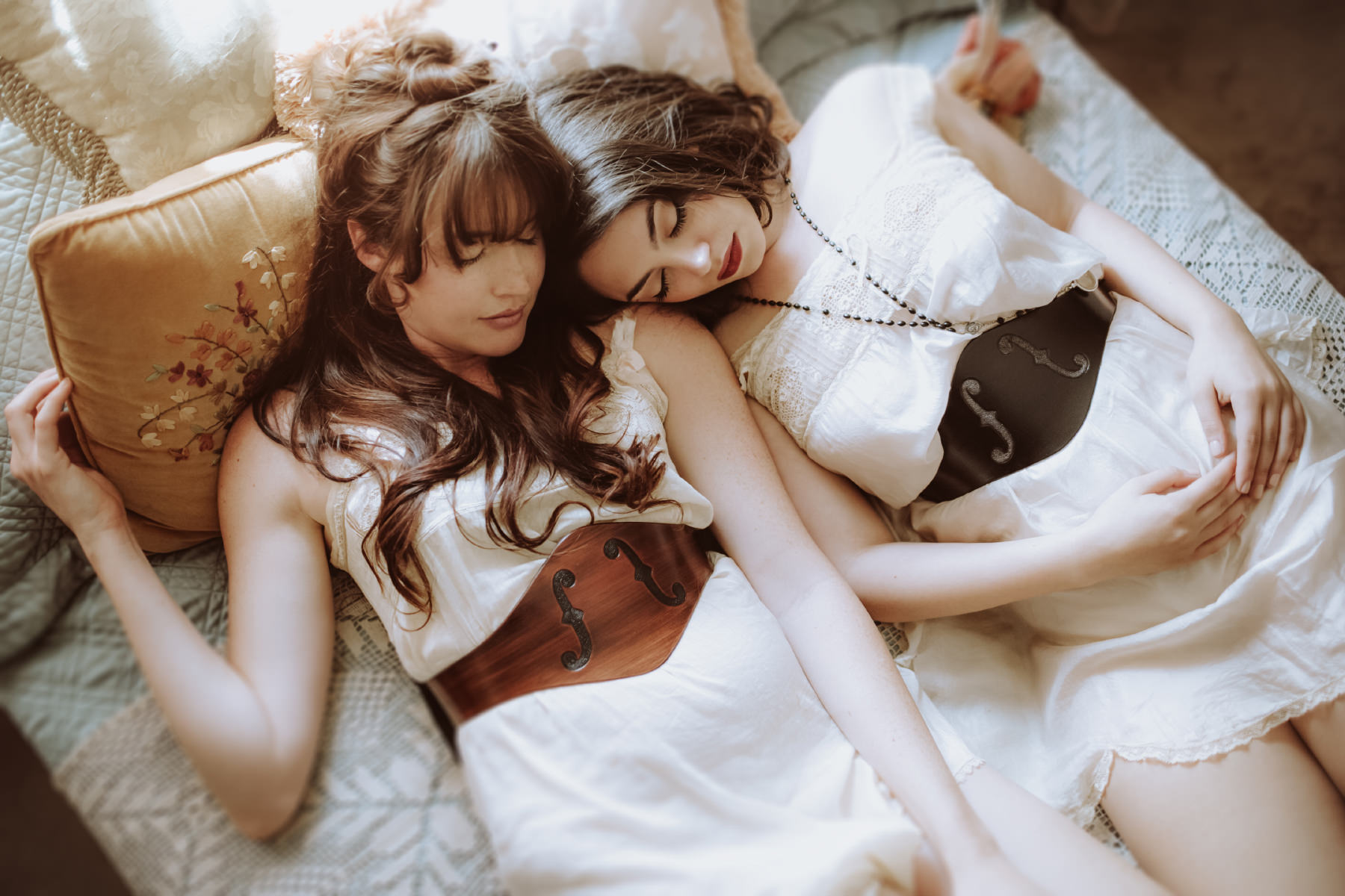 Two models sleeping in a vintage bedroom while wearing Contrived to Charm custom leather belts