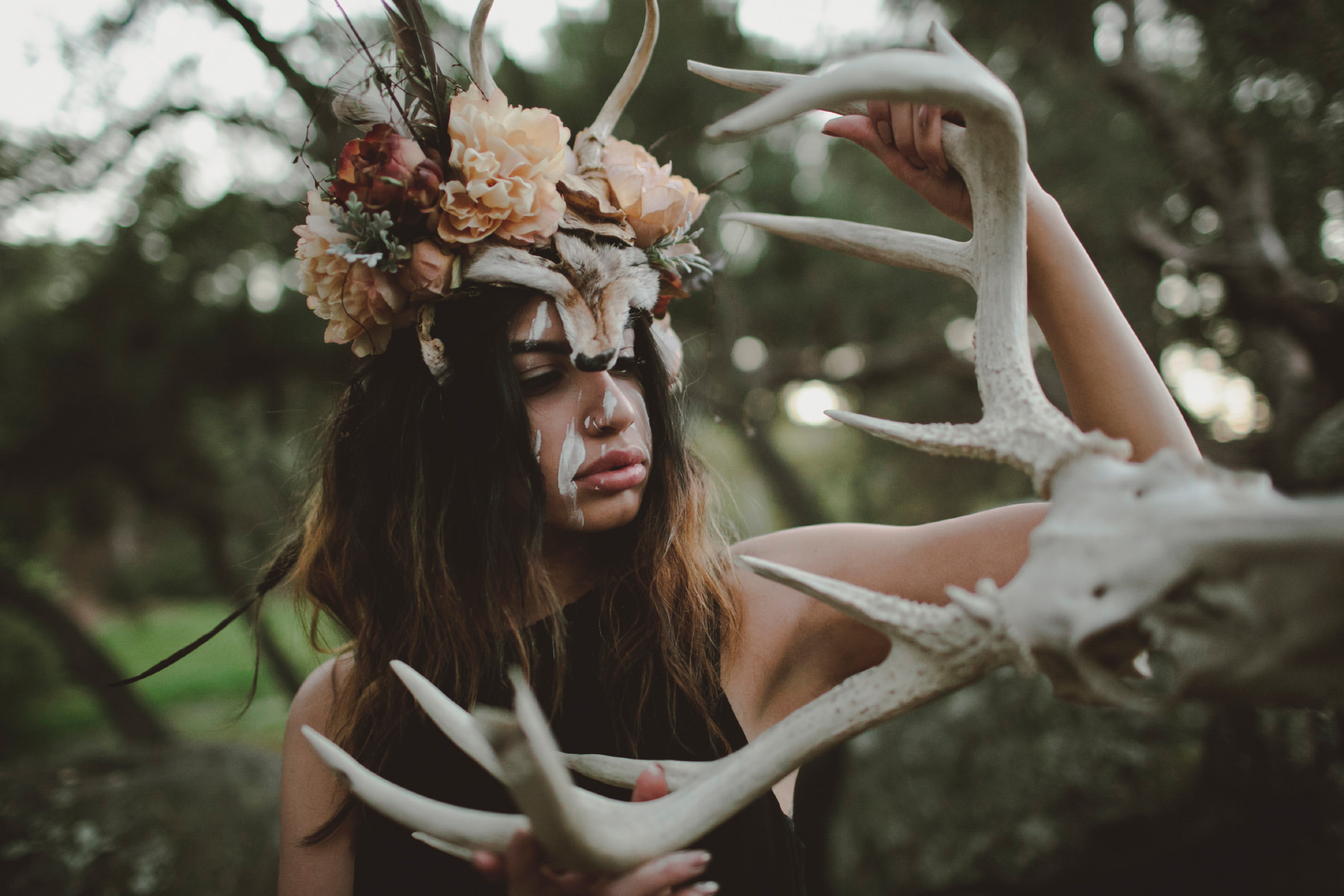 Model Alexandra Sweiss wearing a coyote and antler headdress while holding a deer skull for a Being As An Ocean music video