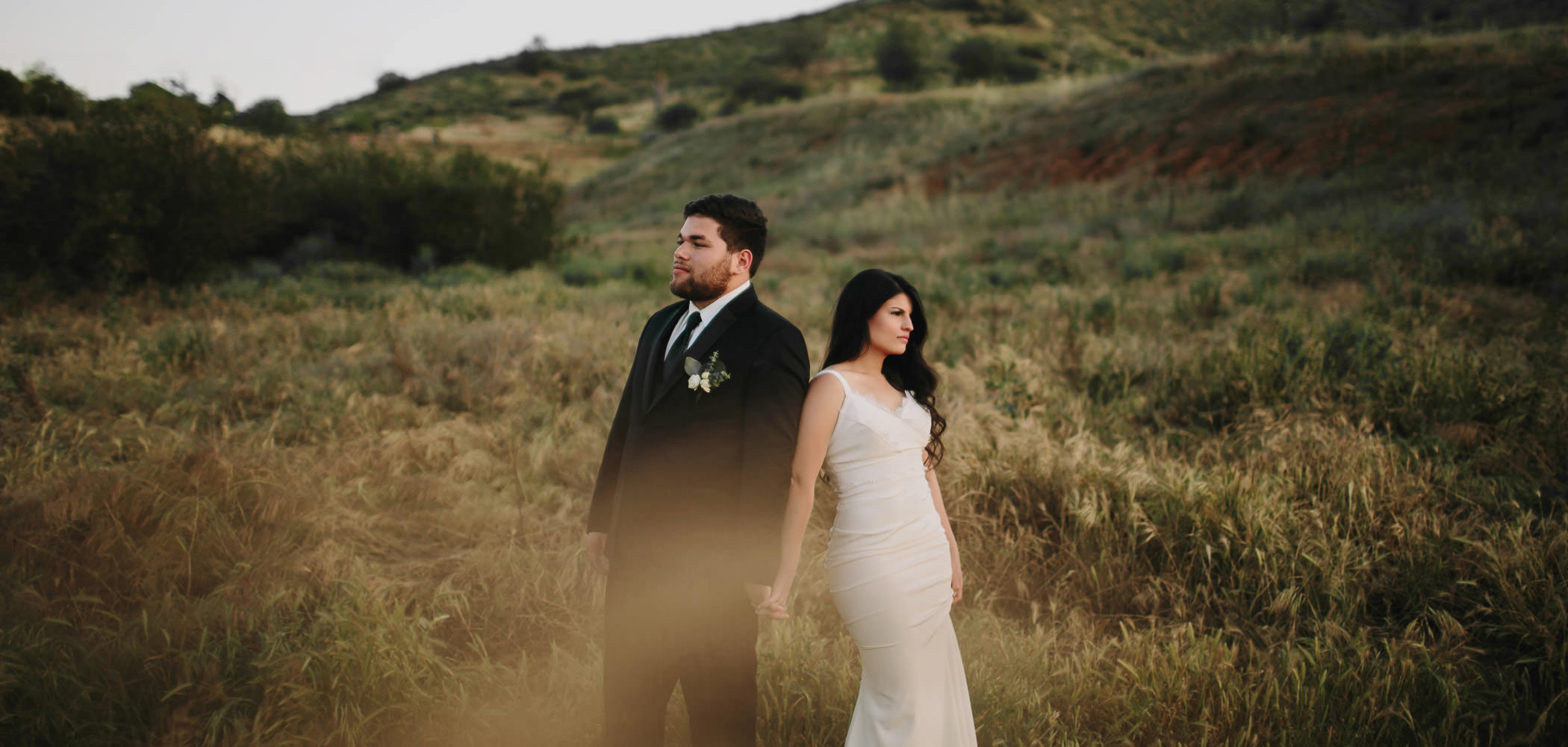 Bride and groom posing in a field at golden hour in Escondido