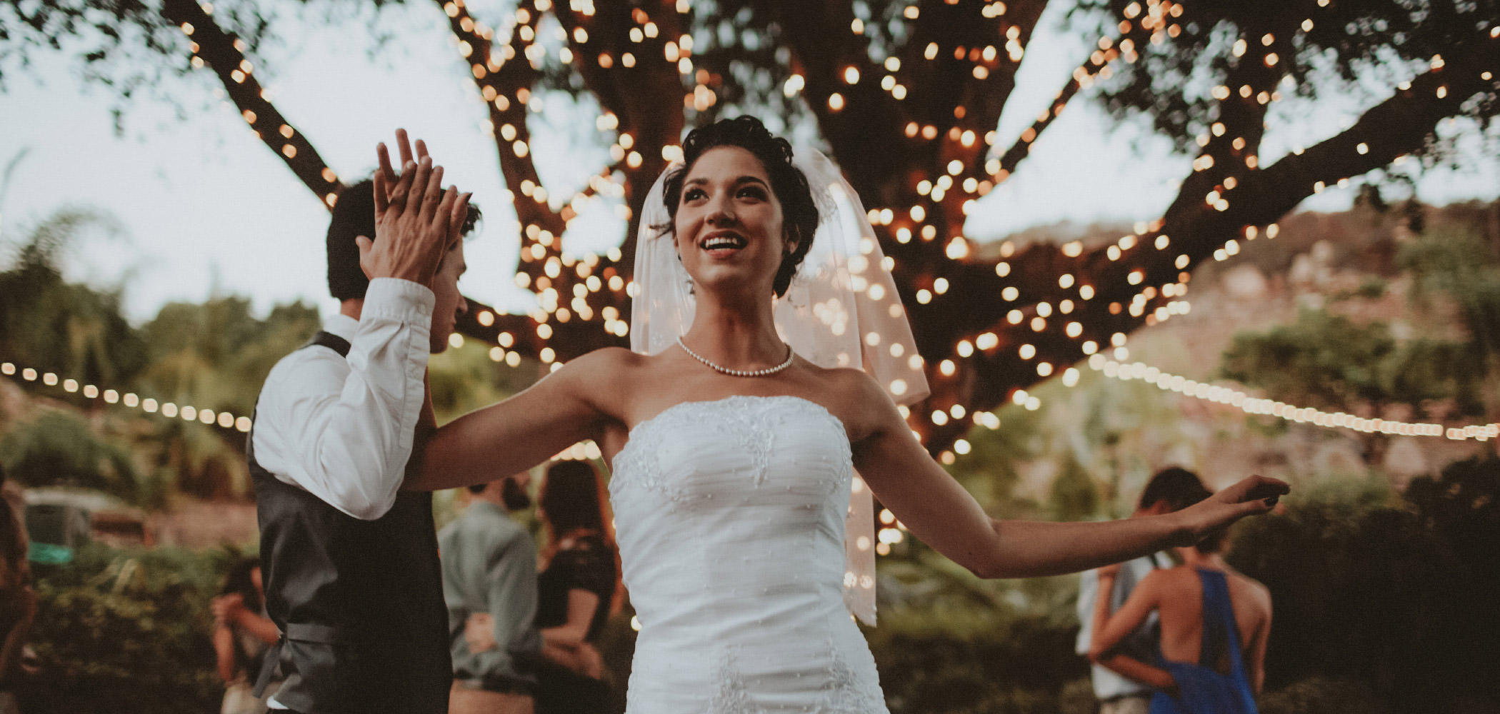 Gorgeous bride dancing with twinkle lights behind her at a San Diego backyard wedding