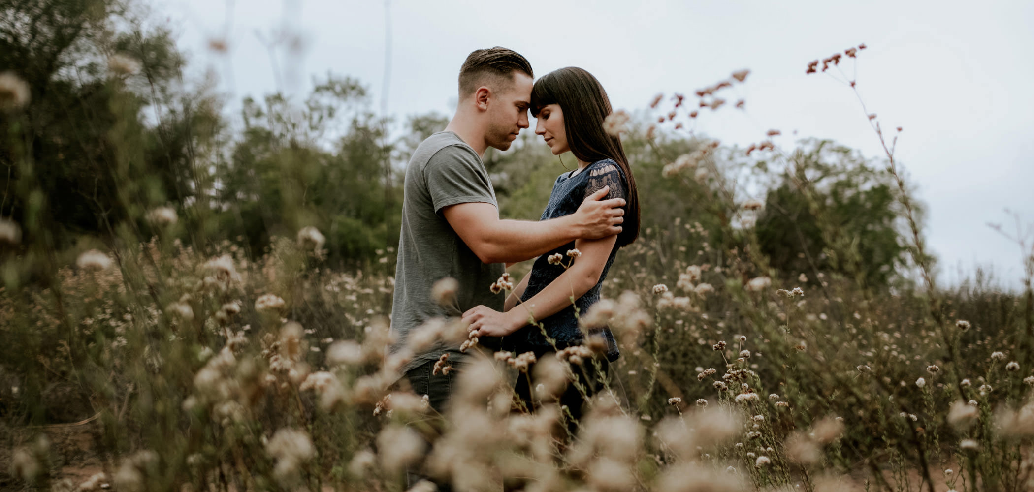 Couple holding each other in a field of wildflowers at Felicita Park in Escondido