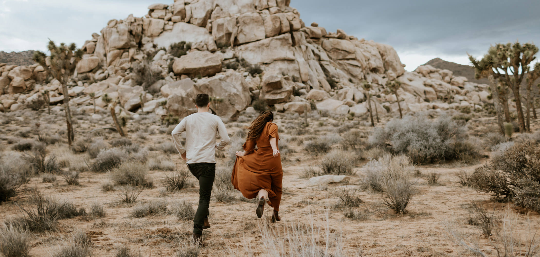 Adventurous couple running towards rocks at Joshua Tree