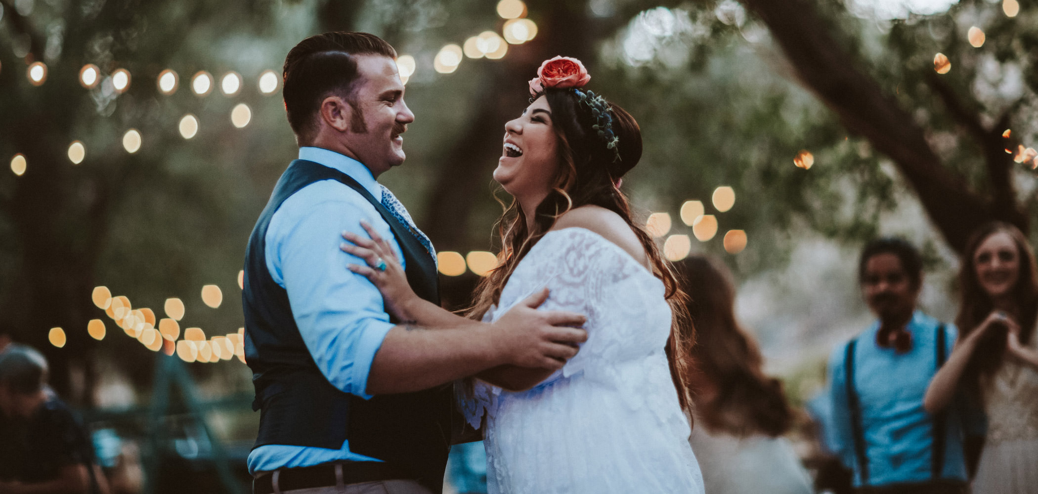 Bride and groom laughing during their first dance with twinkle lights behind them at a Hidden Oaks Ranch