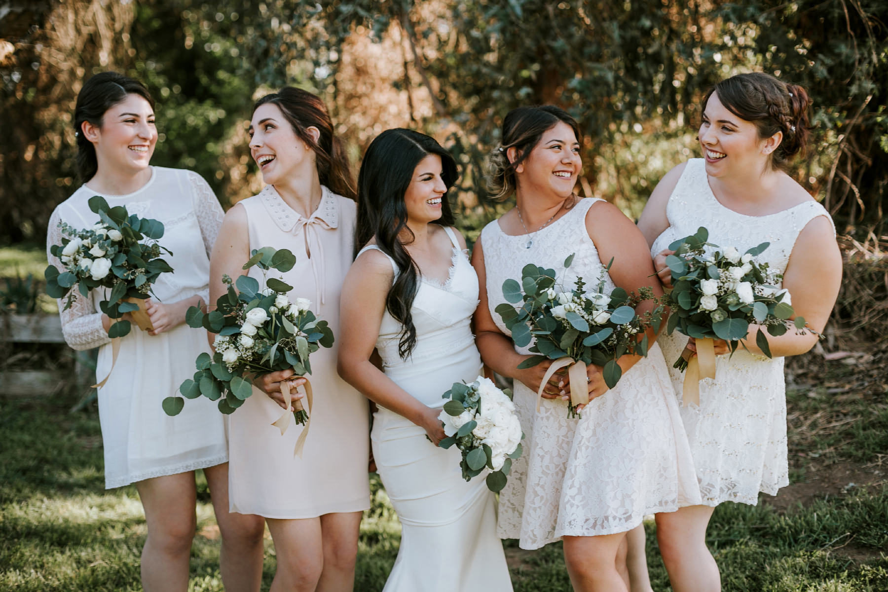 Bridesmaids with mix match white dresses and eucalyptus greenery bouquets