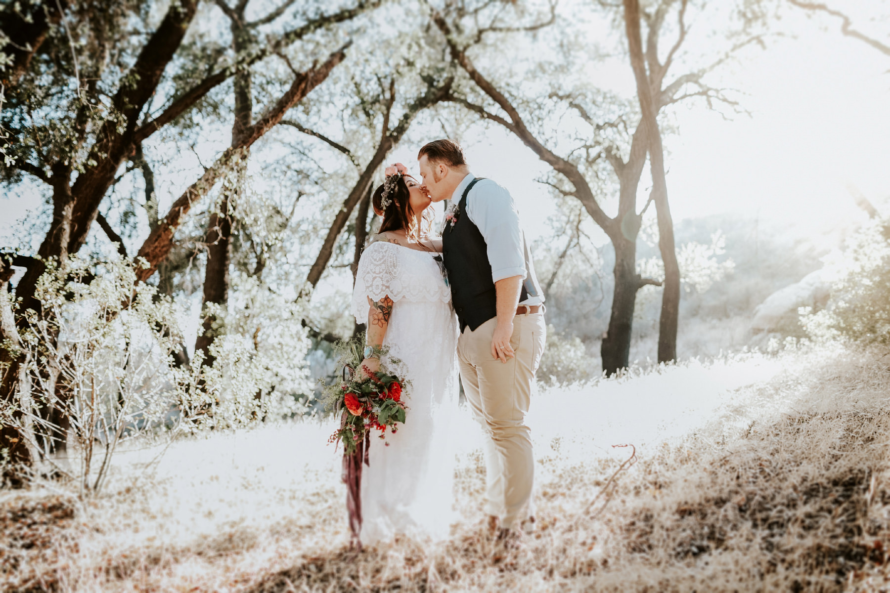 Boho bride and groom kissing in wooded field at golden hour at Hidden Oaks Ranch