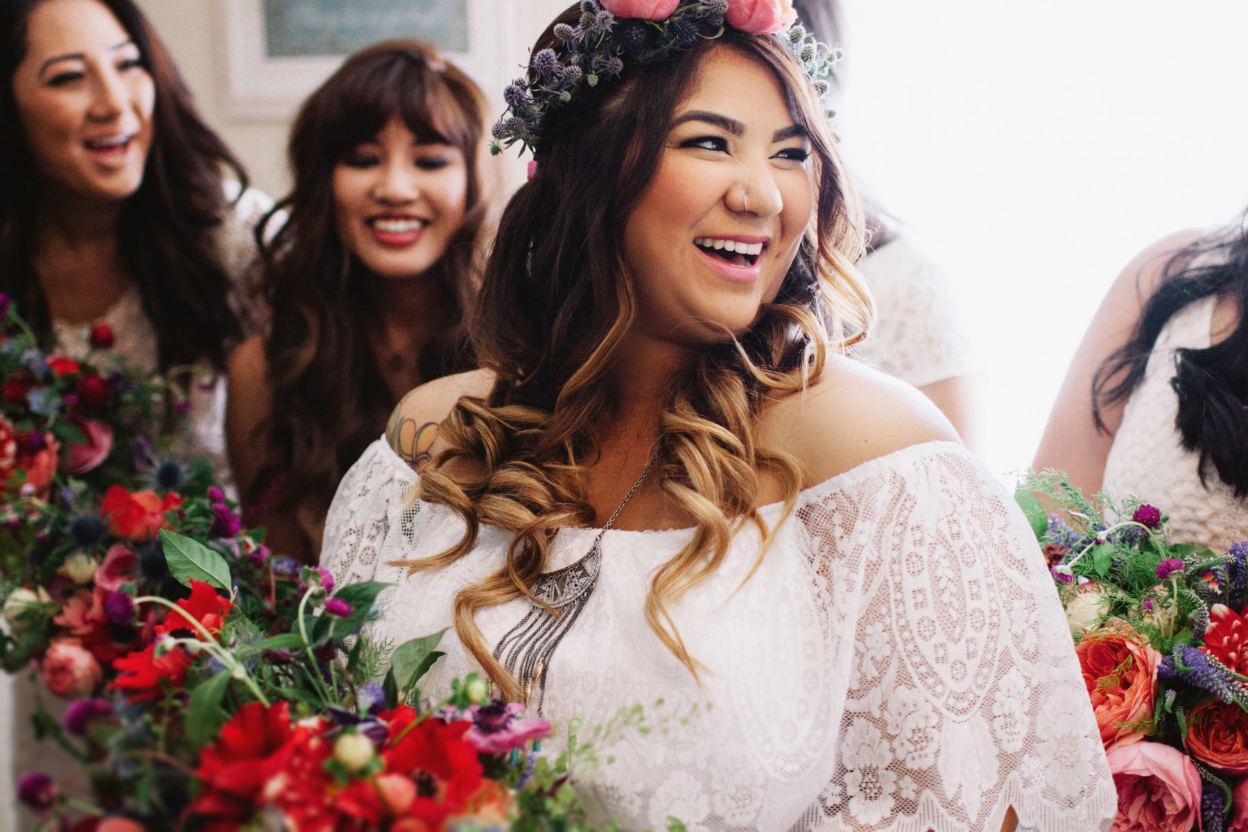 Boho bride wearing a thistle and peony flower crown laughing with bridesmaids