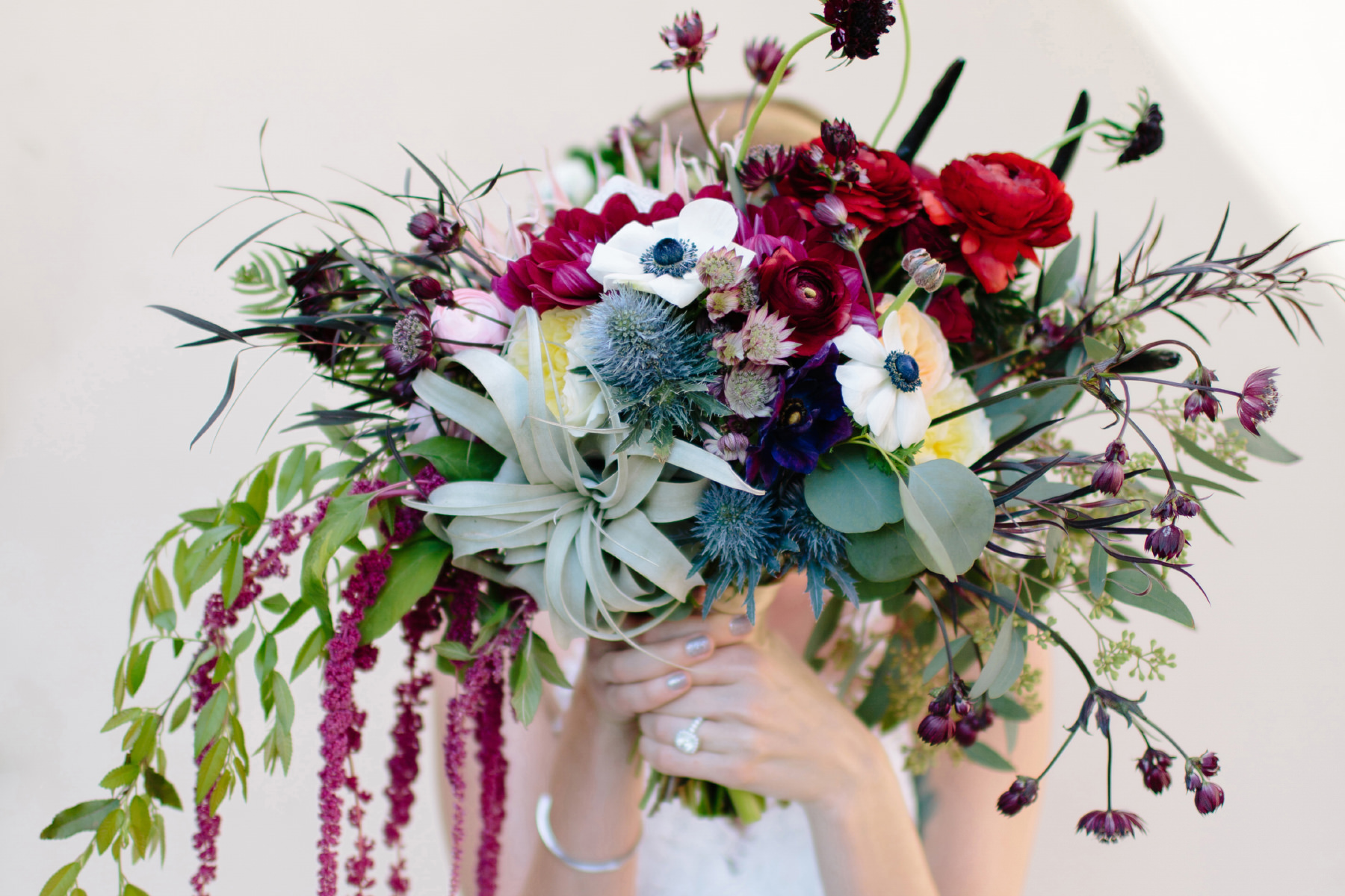 Bride holds cascading bouquet designed by Organic Flora with air plants and greenery