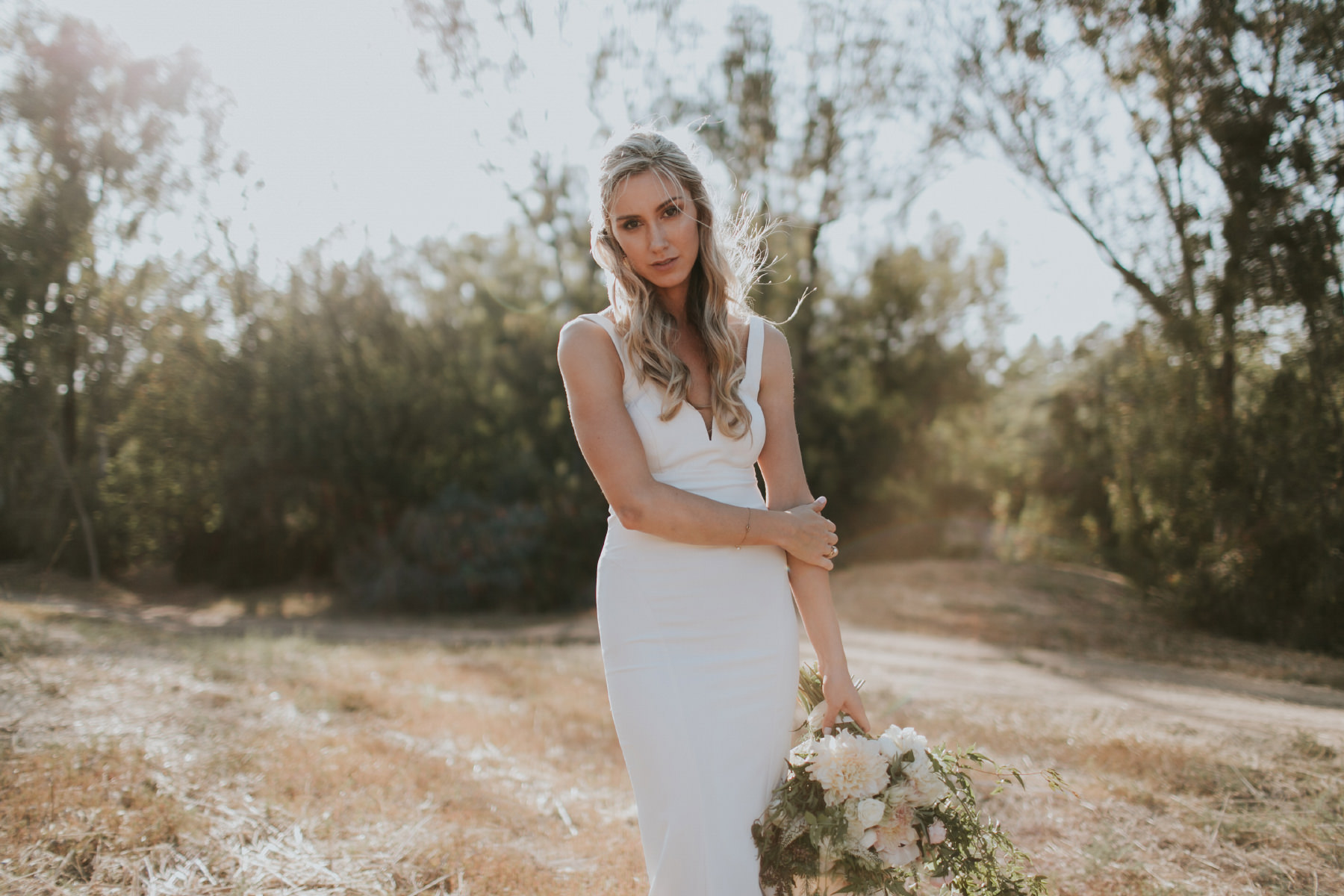 Editorial pose of bride in golden field in Rancho Sante Fe