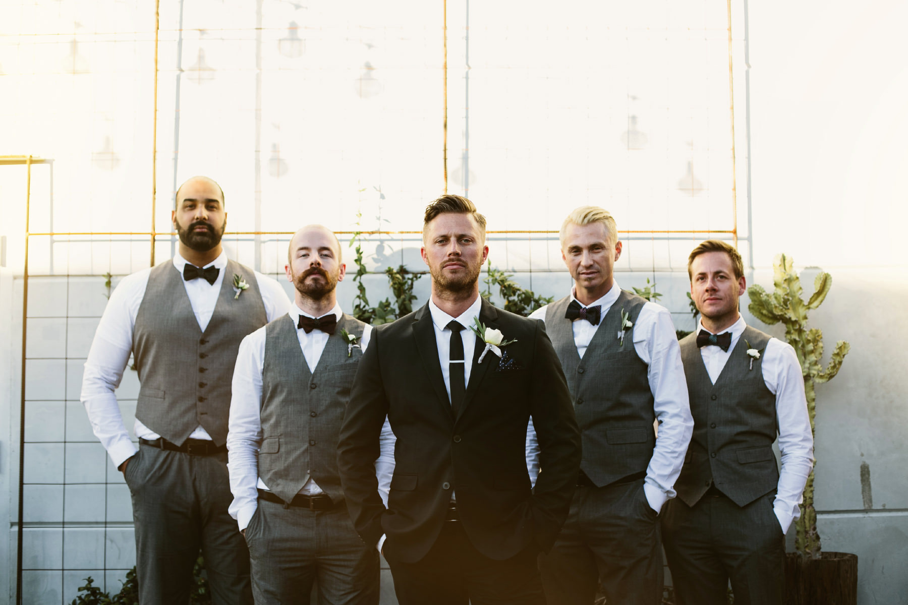 Groom posing with his groomsmen wearing grey vests and bowties at Booze Brothers in San Diego