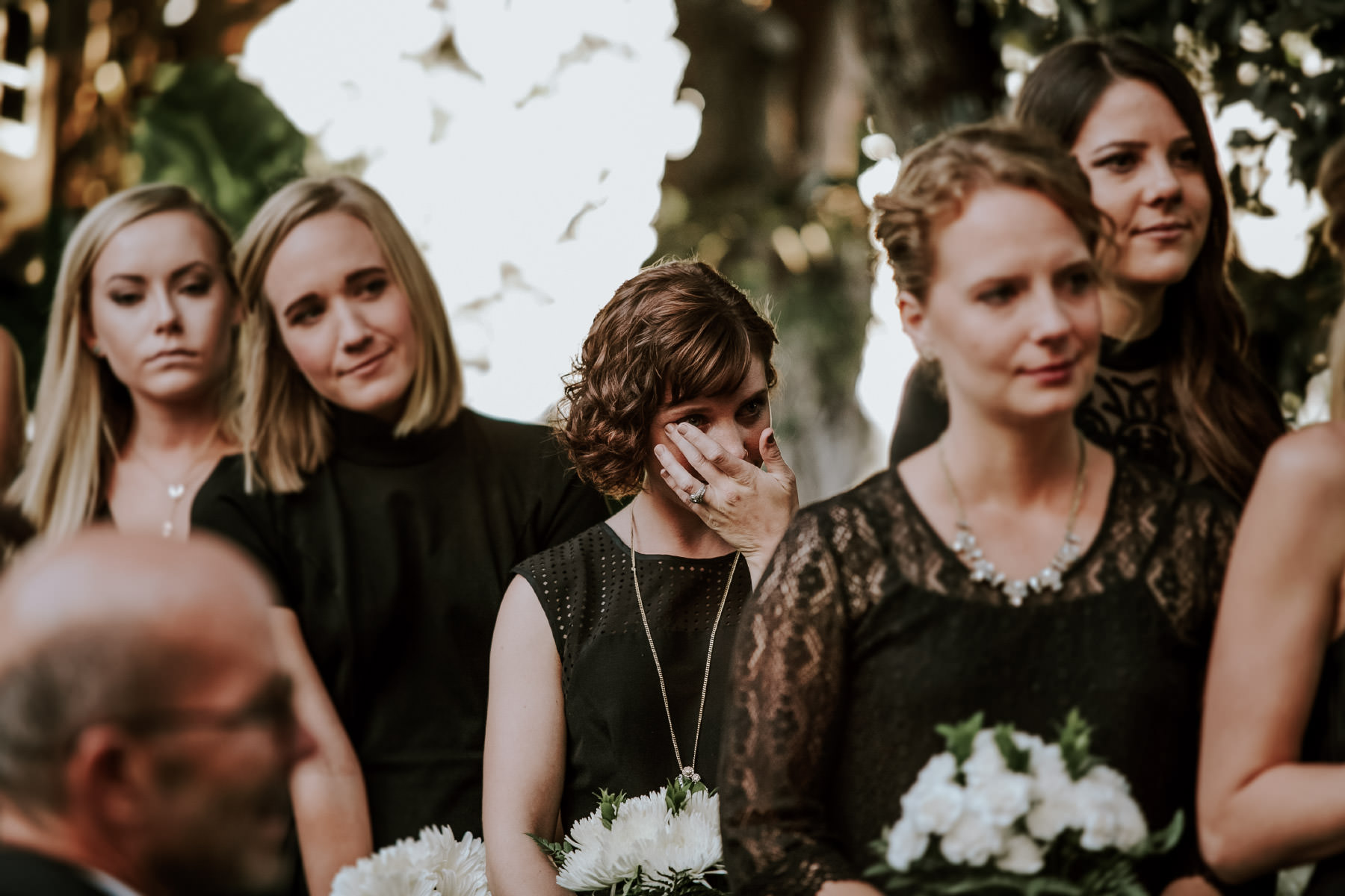 Bridesmaids in black dresses crying at San Diego Botanic Garden wedding