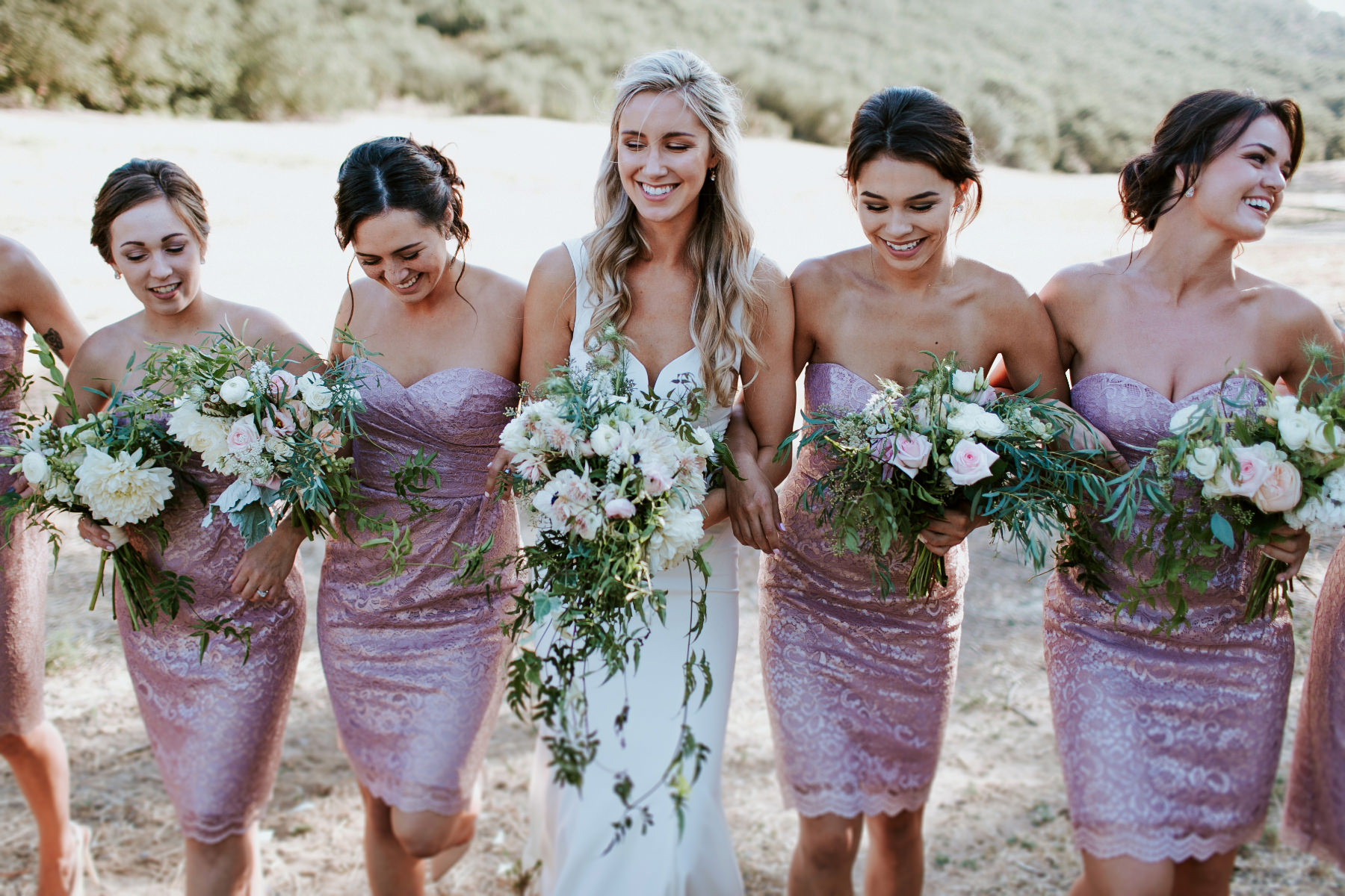 Bridesmaids in metallic dresses with cascading greenery bouquets