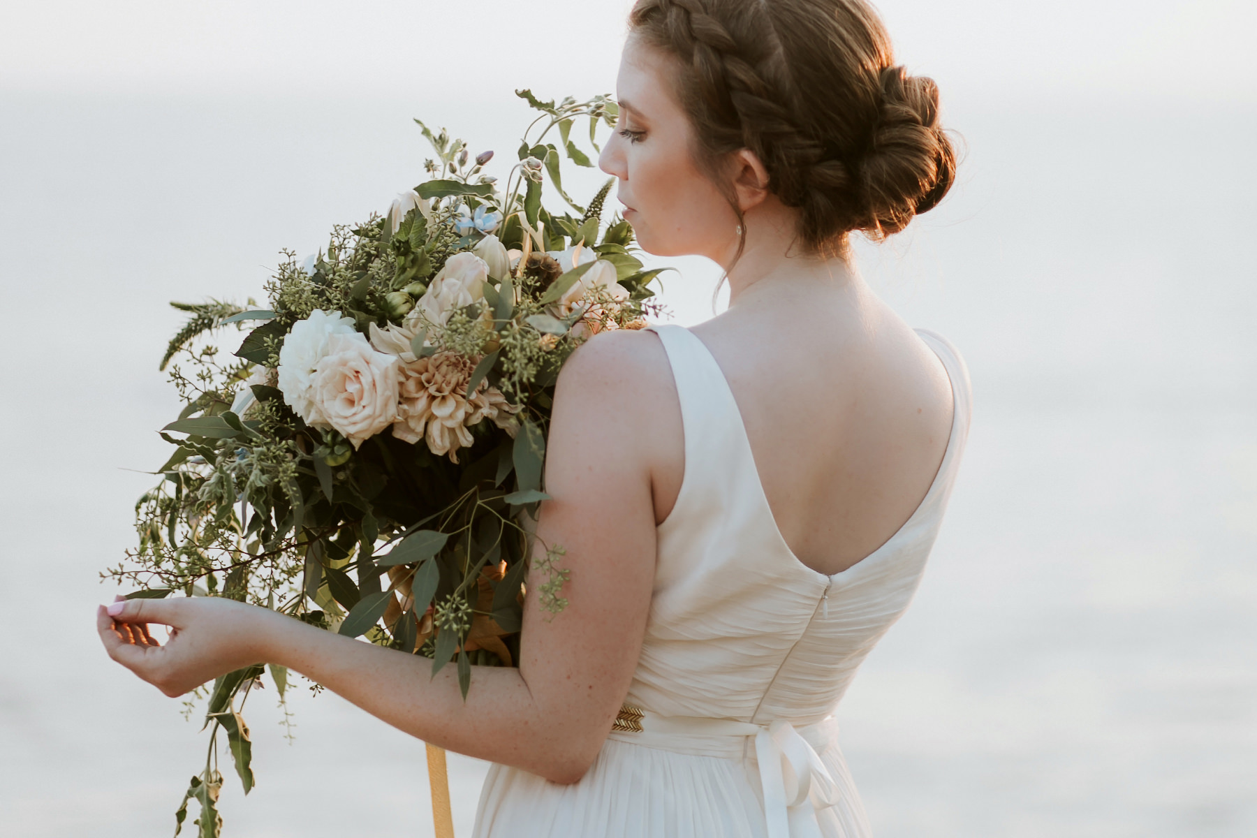 Clean modern bride pose with huge greenery bouquet at Sunset Cliffs in San Diego