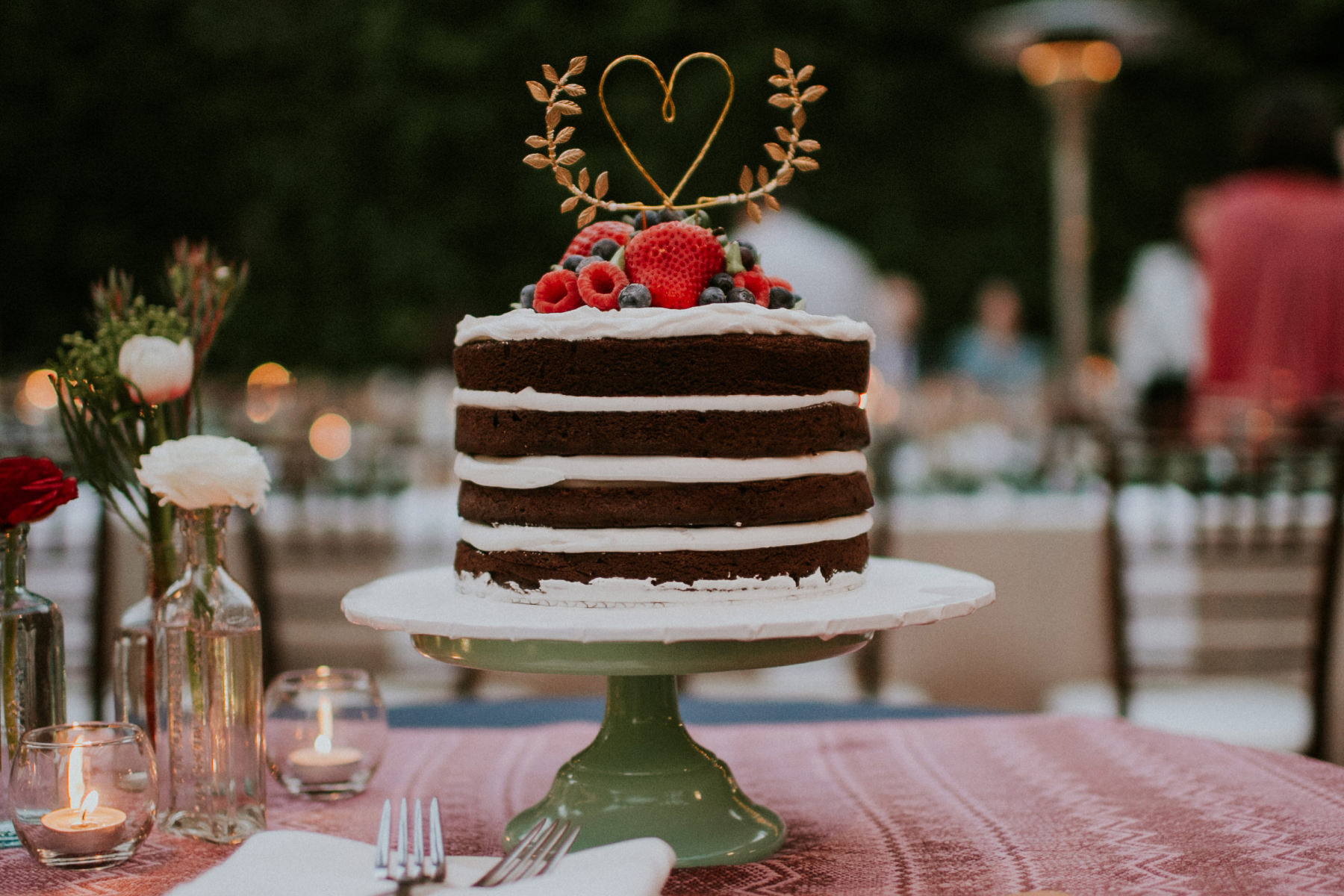 Simple naked chocolate cake with berries and heart wire topper