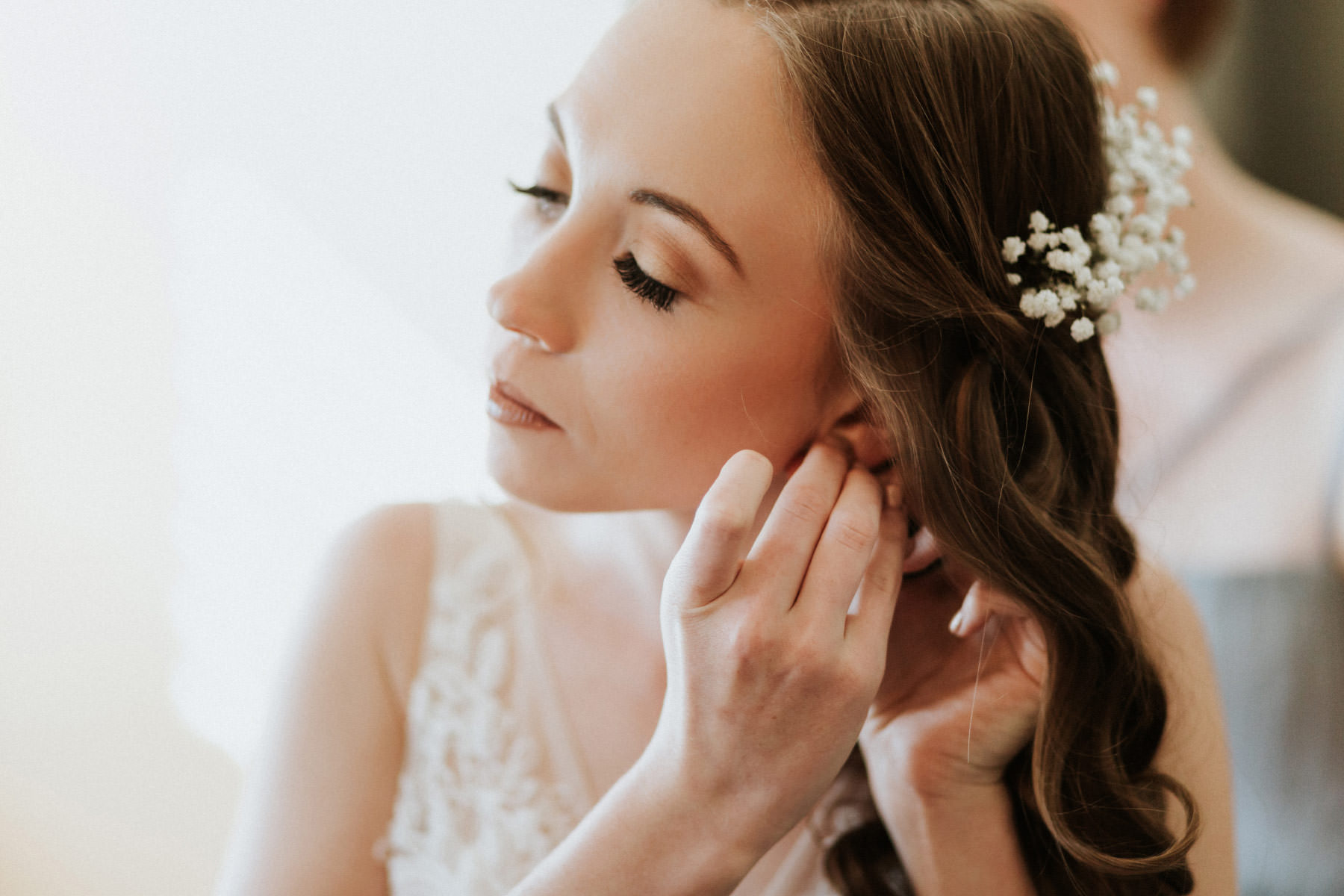 Bride putting on earrings