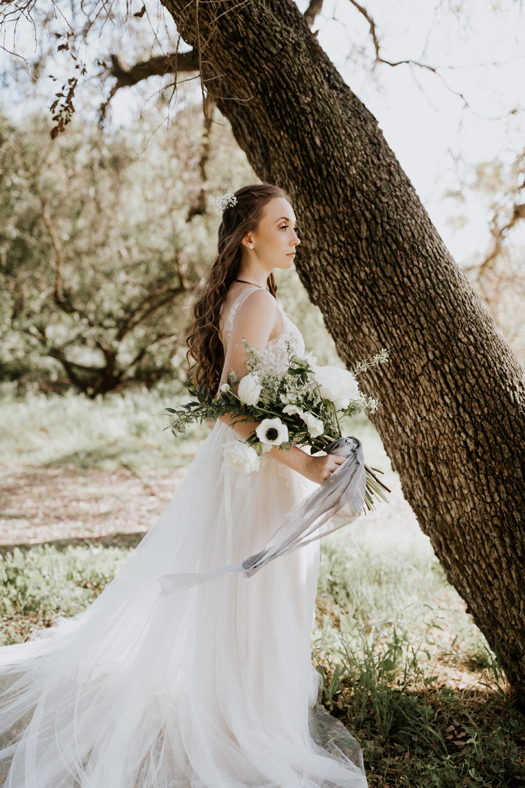 BHLDN dress with bouquet of white roses anemone flowers and raw edge ribbon