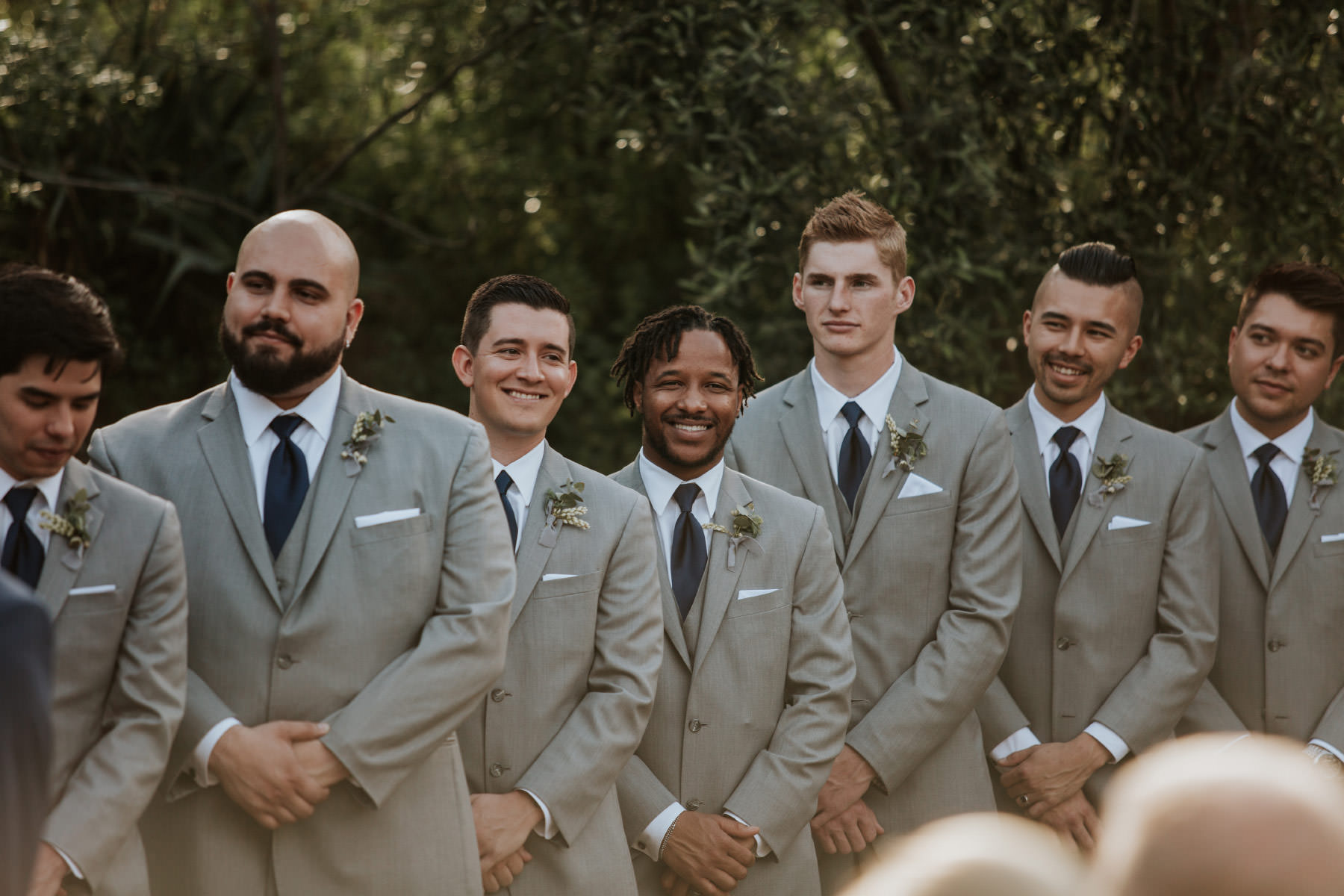 Groomsmen wearing gray suits with navy ties
