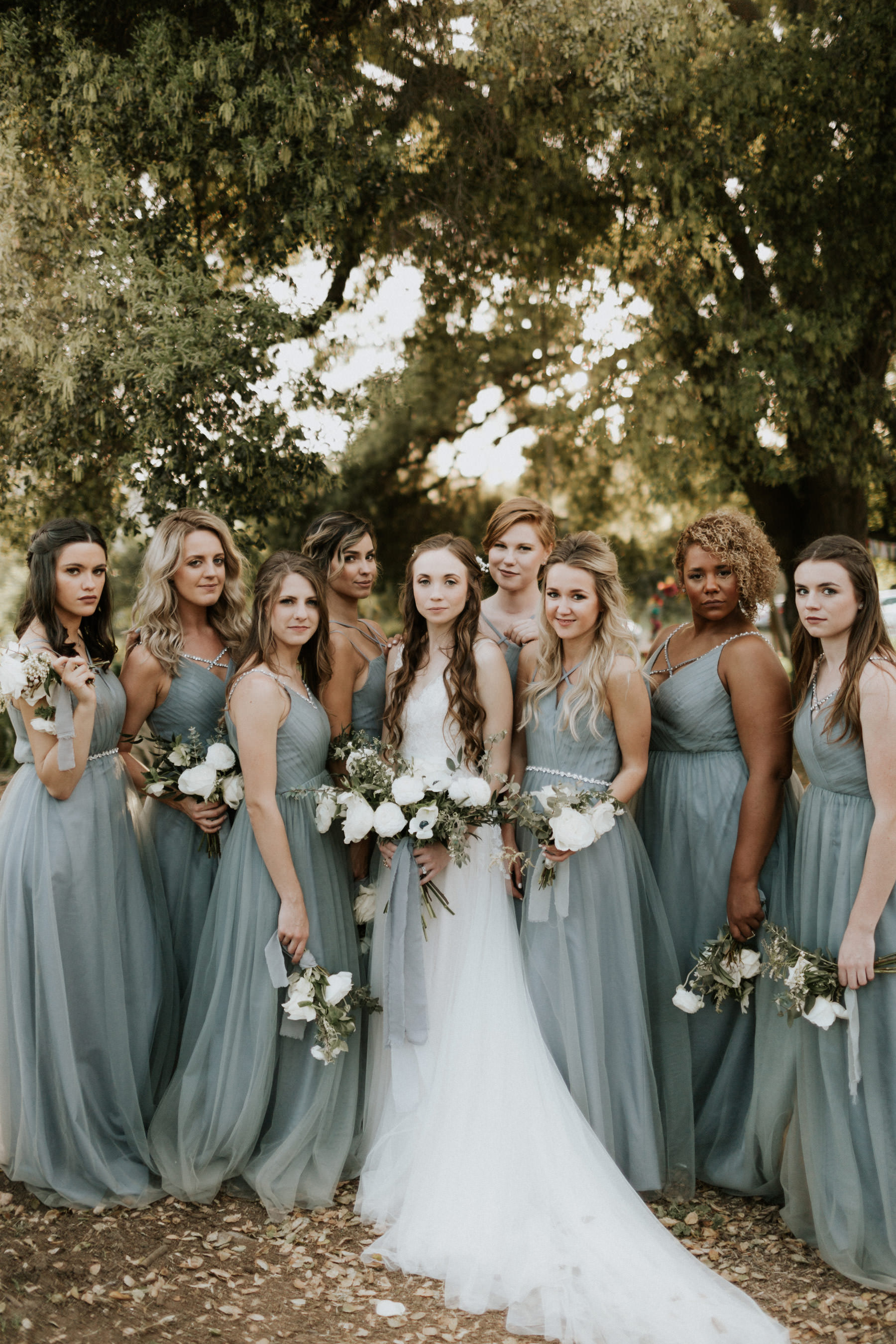 Bridesmaids in dusty blue maxi dresses and bride in BHLDN