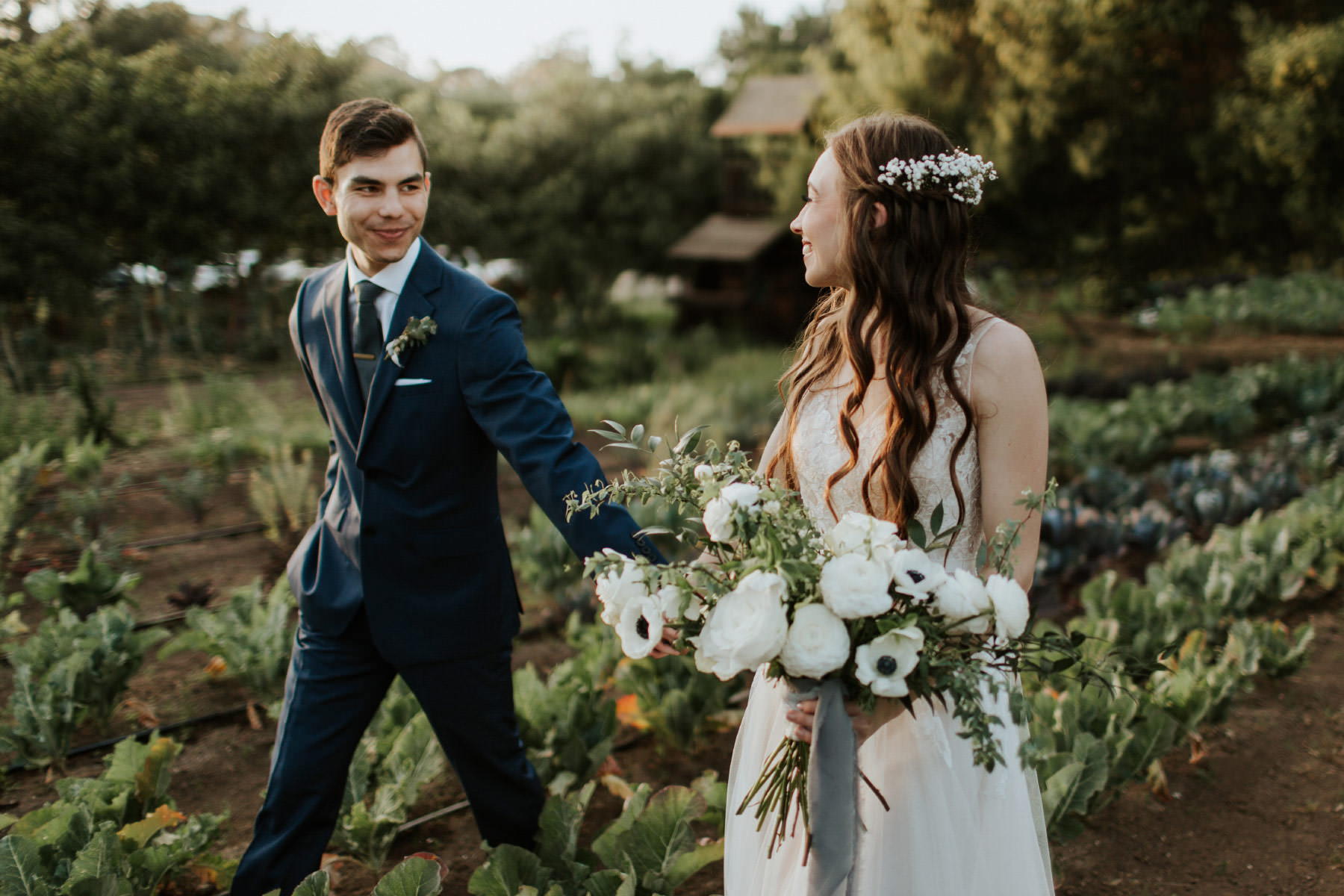 Bride and groom walking through organic garden