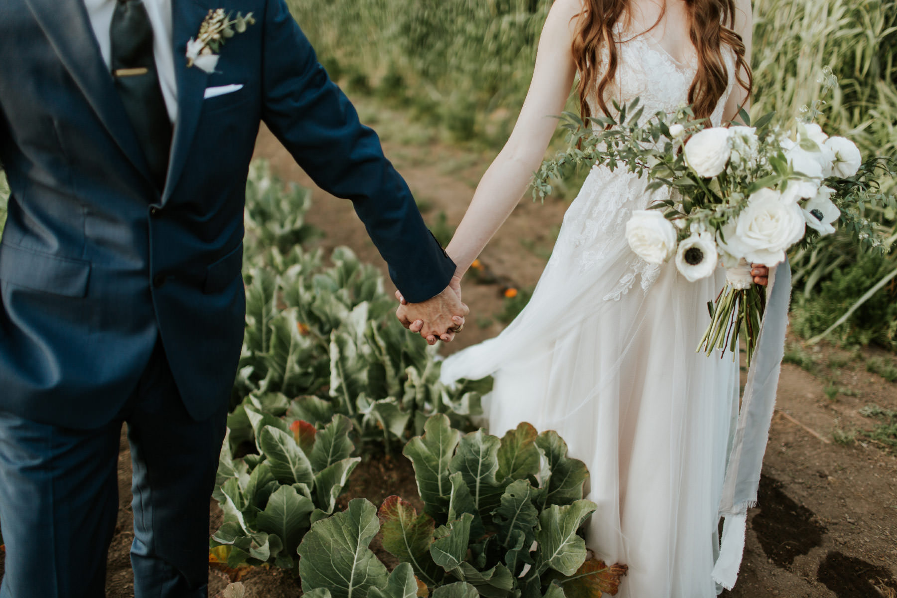 Bride and groom holding hands in organic garden