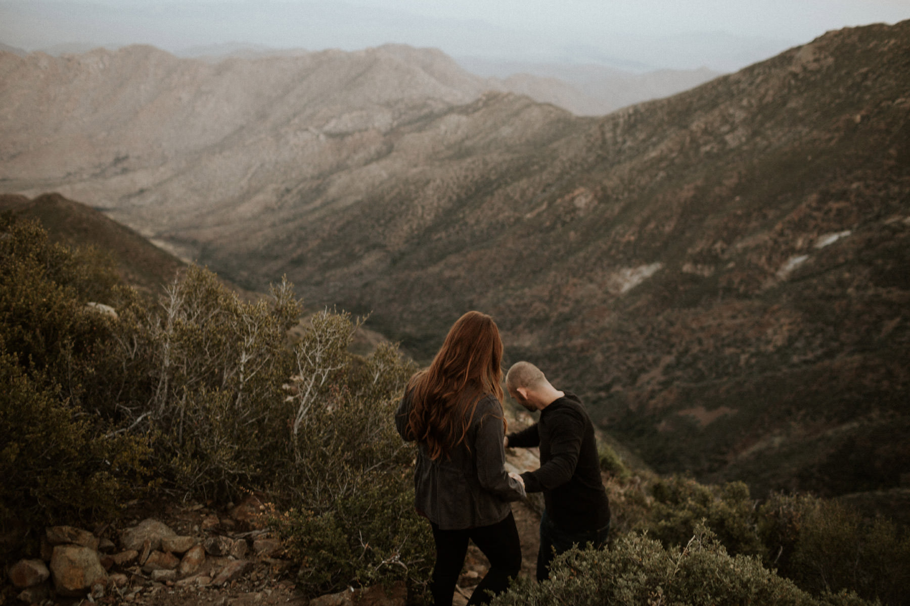 Couple leading each other down a mountain